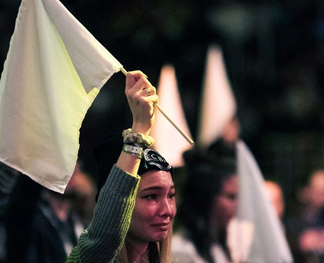 A woman and other in the background holding up a white flag in the Urbana 18 conference