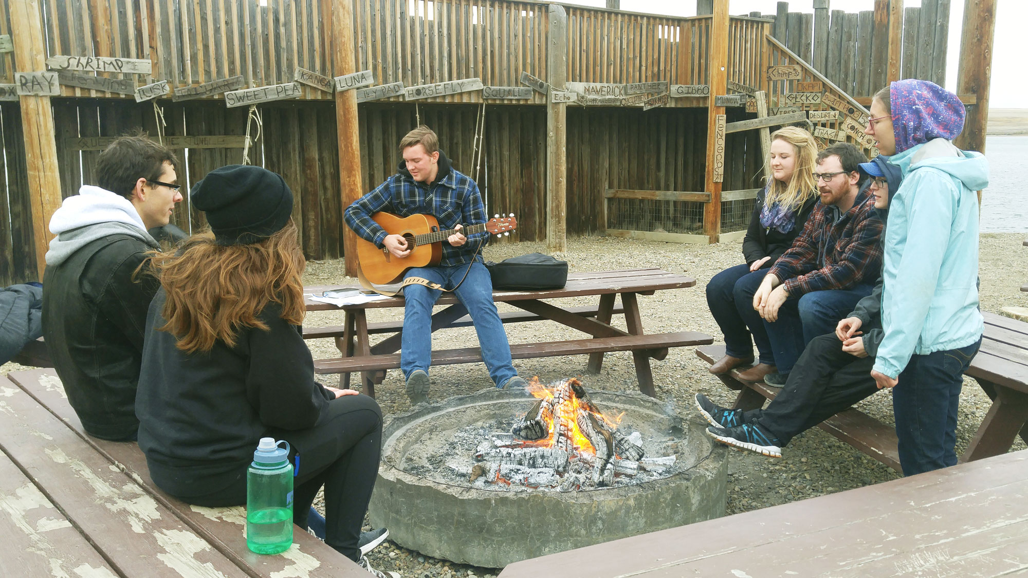 University of Lethbridge students sitting around a camp fire