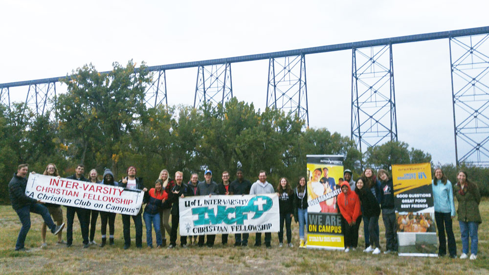 University of Lethbridge students posing for a group photo with signs promoting the group
