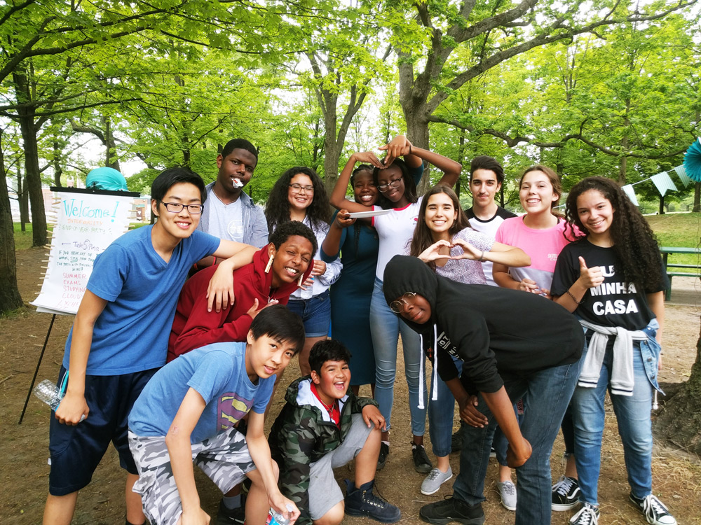 InterVarsity group high school students posing fora group picture outside near the trees