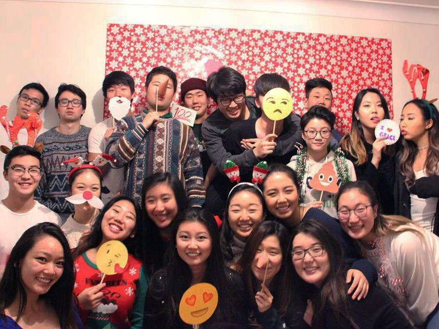 Queens University students posing for a group picture with at a Christmas party