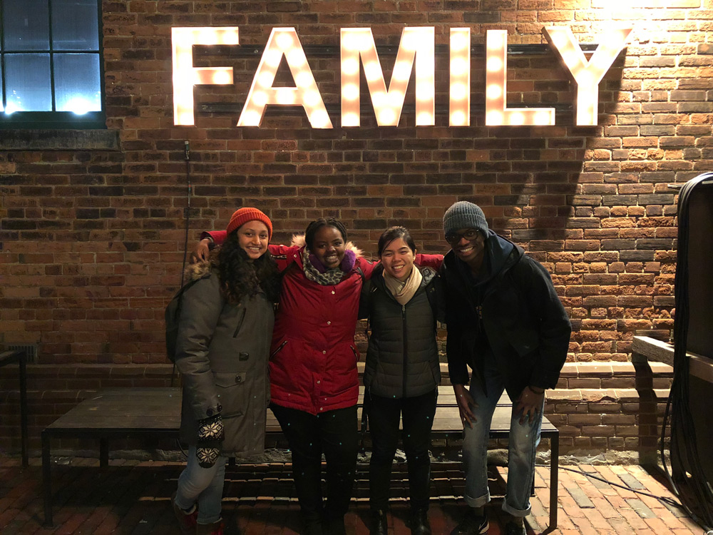 Ryerson University students posing for a picture in front of a sign that reads family