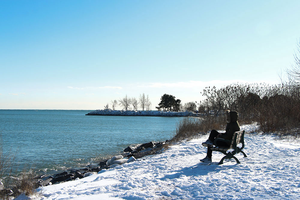 A photo of someone sitting on the bench in the winter in front of a lake