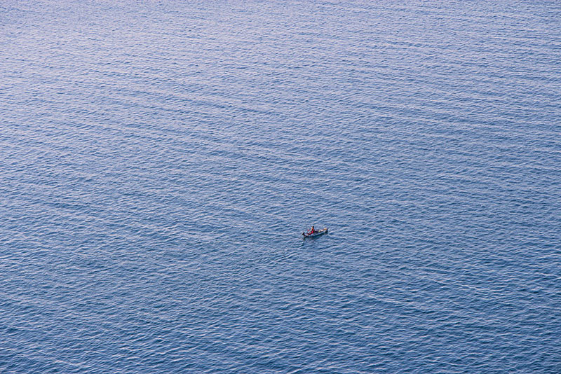 A photo of a small boat floating in the middle of the water