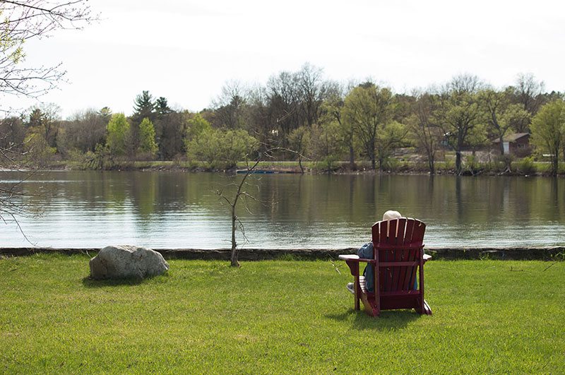 A photo of a person sitting on a chair in front of a lake