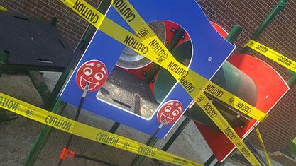 "A ""caution"" yellow tape taped around a playground"
