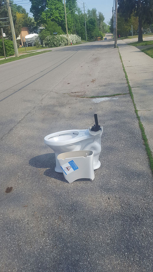A photo of an abandoned broken toilet in the middle of a road