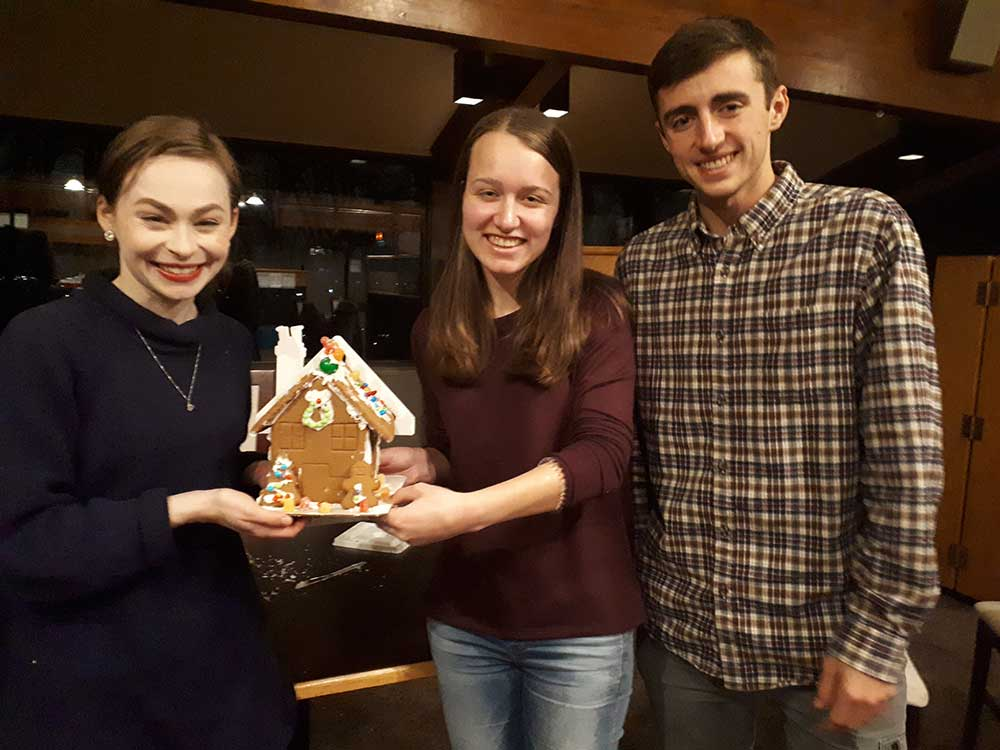 Brock University students holding a gingerbread house