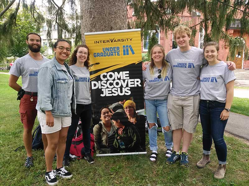 Students from University of Guelph posing beside an InterVarsity banner on campus