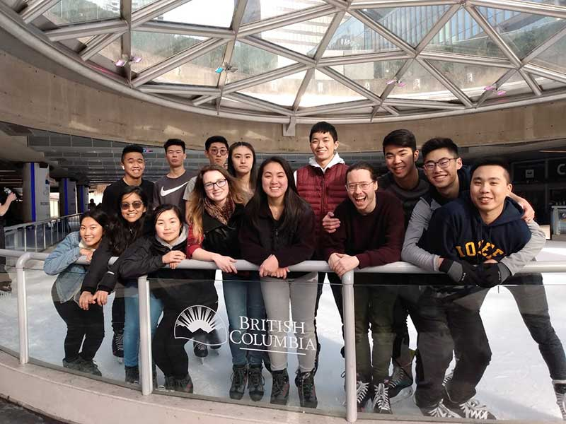 Simon Fraser University students posing for a group photo at a skating rink