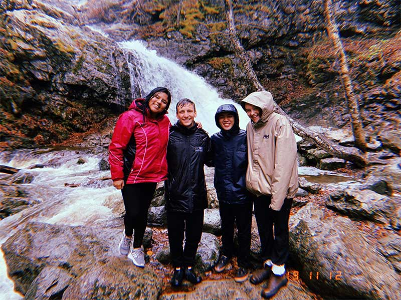 Dalhousie students posing for a group picture in front of a water fall