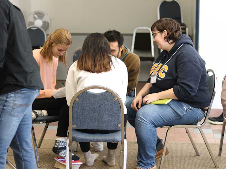 University of Manitoba students praying together in a group