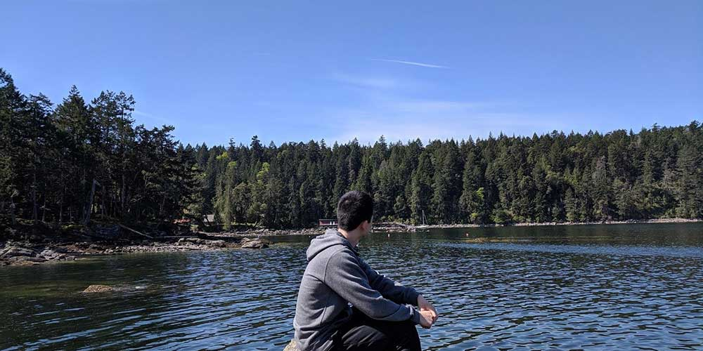 Photo of the student author of this article sitting in front of a lake