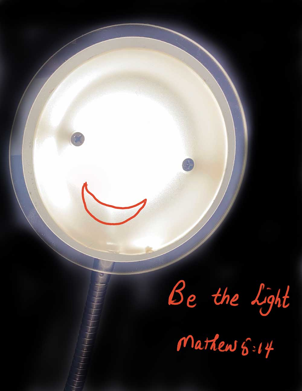 """A close up of a lamp with a black background. The lamp is circular with a wire extension attached to support it. The lamp has two screws placed in the centre of the light forming what look like eyes. Underneath the screws is a red mouth forming an open mouthed smile. In the bottom right corner is red text that reads """"Be the Light, Matthew 5:14""""."""